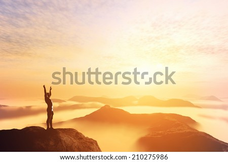 Happy man with hands up on the top of the world, above clouds and mountains. Success, winner, bright future - stock photo