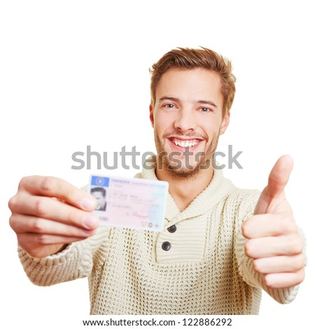 Happy man with his European drivers licence holding his thumbs up - stock photo