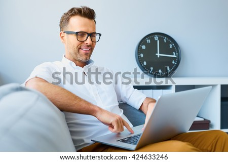Happy man with laptop on the sofa - stock photo