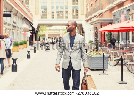 Happy man with shopping bags walking on a street  - stock photo