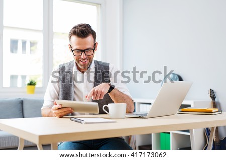 Happy man working from home using digital tablet and laptop