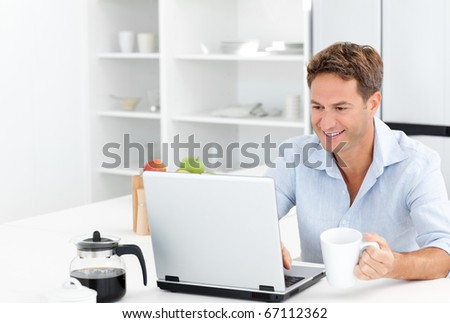 Happy man working on his laptop while drinking coffee in the kitchen - stock photo