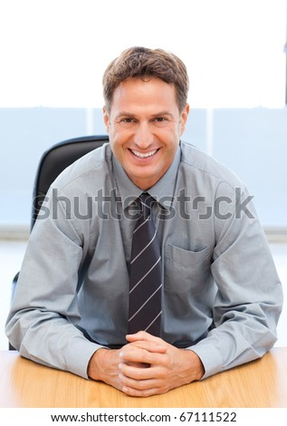 Happy manager sitting at a table in an office - stock photo