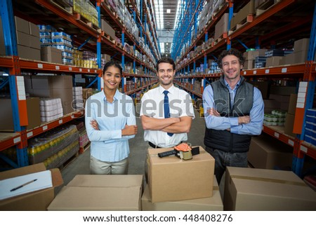 Happy managers are posing in front of cardboard boxes with crossed arms in a warehouse