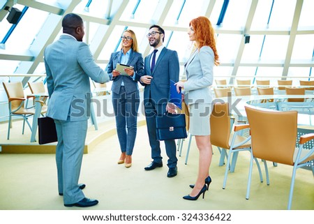 Happy managers in suits discussing morning news in office - stock photo