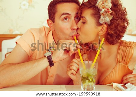 Happy marriage concept. Portrait of a beautiful married couple of hipsters in trendy clothing drinking mojito and kissing in vintage cafe. Wedding day. Close up. Indoor shot