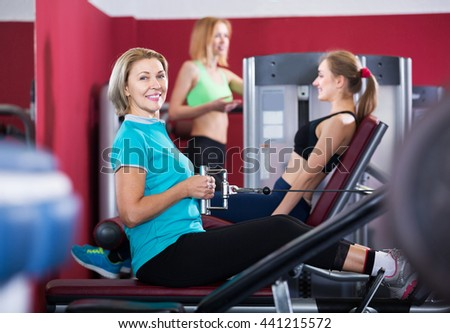 Happy mature and young women doing powerlifting on machines in jym
