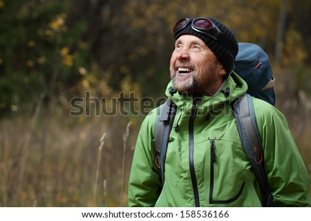 Happy mature backpacker in an autumn forest - stock photo