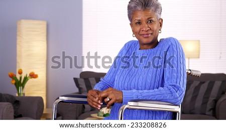 Happy Mature black woman sitting in wheelchair - stock photo