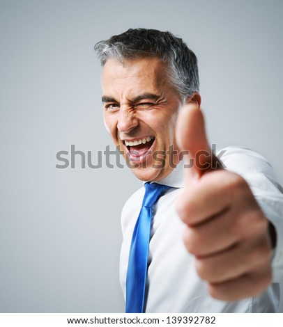 Happy mature business man showing thumbs up sign - stock photo