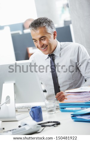 Happy mature business man working in office - stock photo