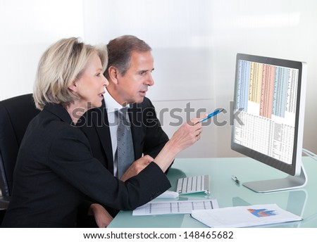 Happy Mature Businessman And Businesswoman Looking At Graph On Computer - stock photo