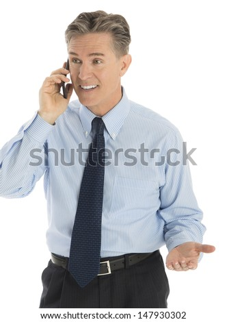Happy mature businessman gesturing while answering smart phone against white background - stock photo