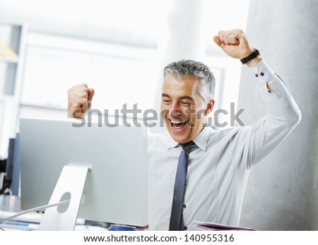 Happy mature businessman in office arms raised. - stock photo