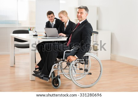 Happy Mature Businessman On Wheelchair With Colleagues In Office - stock photo