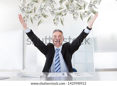 Happy Mature Businessman Raising Arms At Desk In Office - stock photo