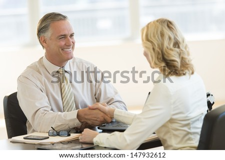 Happy mature businessman shaking hands with female colleague at office desk - stock photo