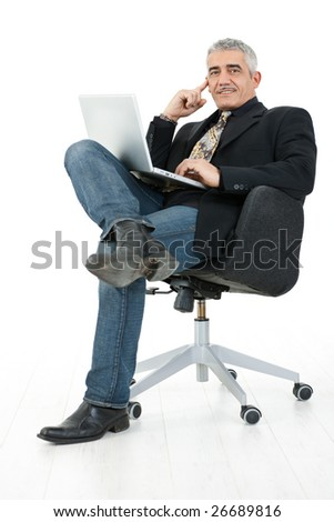 Happy mature businessman sitting in office chair working on laptop computer, smiling, isolated on white background.