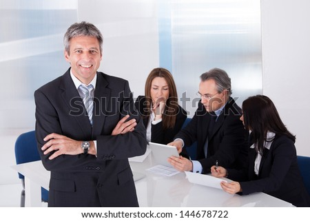 Happy Mature Businessman Standing In Front Of Colleagues In Office - stock photo