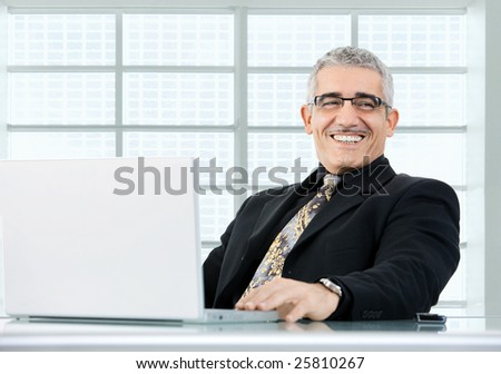 Happy mature businessman working on laptop computer at desk az office, smiling.