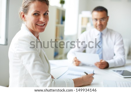 Happy mature businesswoman looking at camera with her colleague on background - stock photo