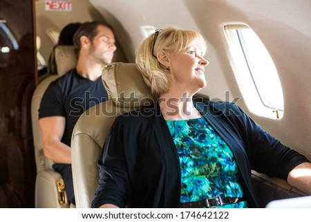 Happy mature businesswoman with man sleeping behind on private jet - stock photo