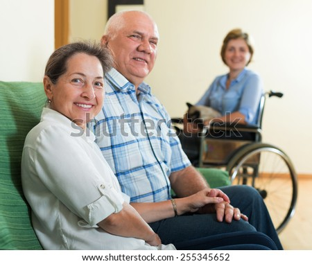 Happy mature couple and adult  daughter in wheelchair  - stock photo