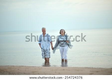 Happy Mature couple enjoy fresh air on beach - stock photo