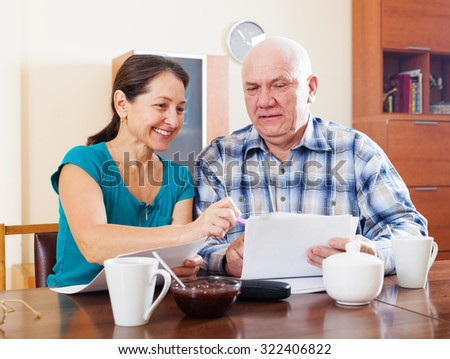 Happy mature couple holding financial documents at home interior - stock photo