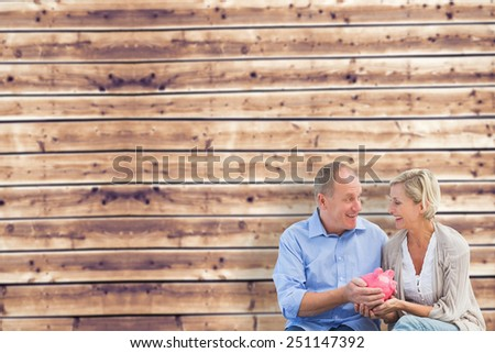 Happy mature couple holding piggy bank against wooden planks background - stock photo