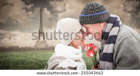 Happy mature couple in winter clothes with roses against paris under cloudy sky
