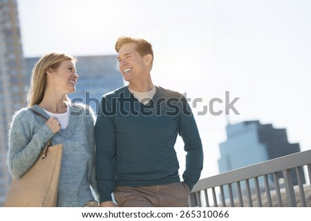 Happy mature couple looking at each other in city against clear sky - stock photo