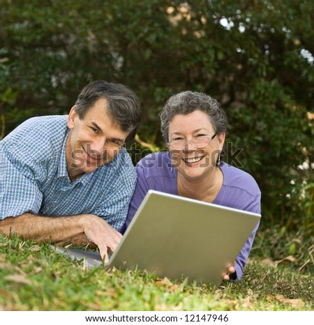 Happy mature couple lying in the grass and working on their laptop