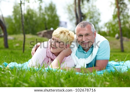 Happy mature couple lying on grass in the countryside