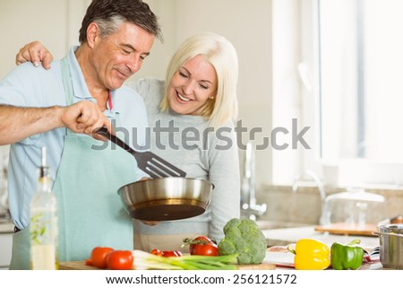 Happy mature couple making dinner together at home in the kitchen - stock photo