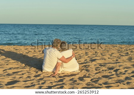 Happy Mature couple on beach against the sky - stock photo