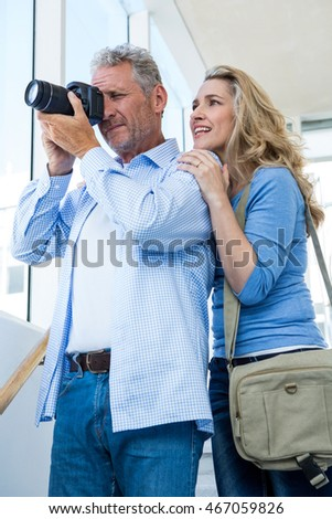 Happy mature couple photographing with camera at home