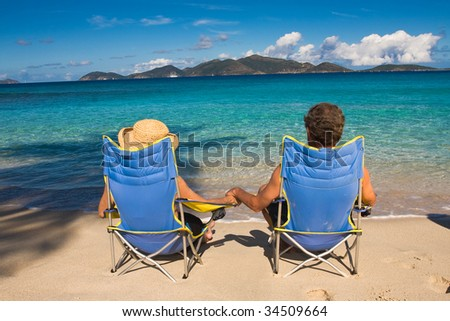 happy mature couple posting on a beach - stock photo