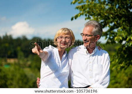 Happy mature couple - senior people (man and woman) already retired - having a walk in summer in nature