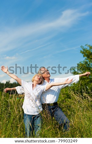 Happy mature couple - senior people (man and woman) already retired - having fun in summer in nature - stock photo