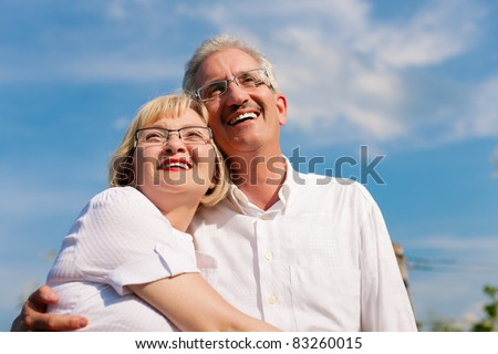 Happy mature couple - senior people (man and woman) already retired - looking to the blue sky in summer