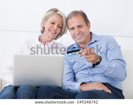 Happy Mature Couple Shopping Online On Laptop At Home - stock photo