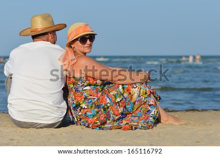 Happy mature couple sitting at seashore on sandy beach back to back on summer outdoors background - stock photo
