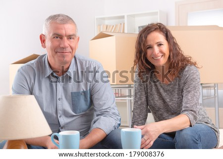 Happy mature couple sitting in their new home and drinking coffee or tee, boxes in background