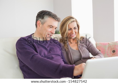 Happy mature couple sitting on a sofa and looking at laptop