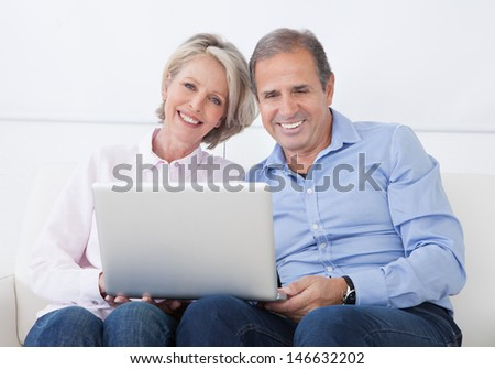 Happy Mature Couple Sitting On Couch And Working On Laptop