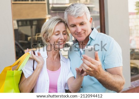 Happy mature couple taking a selfie together in the city in the city on a sunny day