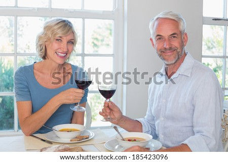 Happy mature couple toasting wine glasses over food against the window at home
