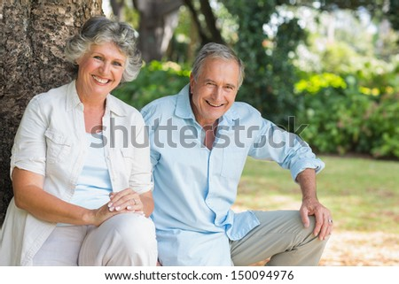 Happy mature couple together sitting in park by tree - stock photo