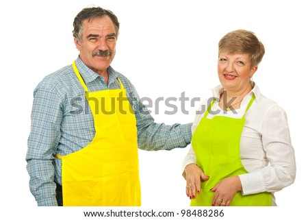 Happy mature couple with green and yellow apron isolated on white background